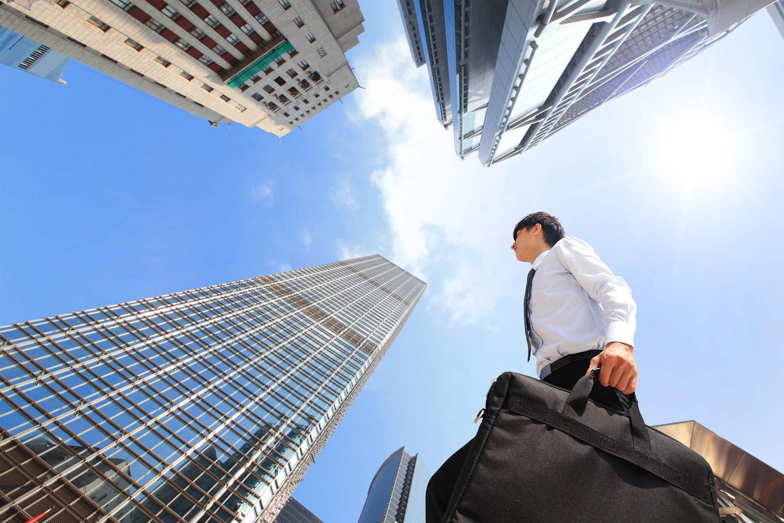happy successful business man outdoors Next to Office Buildings with cityscape and sky hong kong asia asian